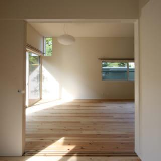 1階ゲストルームからリビングを見る。正面の公園側の壁は、左上に小さなハイサイド窓が。公園の大木の緑が見える場所につくられており、高い位置でも視線が抜けて気持ちがいい