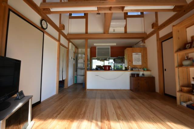 居間からキッチンを見る。上に見える二つの窓を開けると、テラスに続く掃き出しから居間を抜ける風の通り道ができる。緑豊かな庭の木立を通って入る風は心地よく、H様も穏やかなひとときを過ごされているという