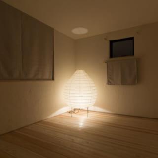 2階寝室。部屋を照らすのは、正面の照明器具のみ。照明器具は消耗しにくく長く使えるため、こだわりのものを探すとよいという。正面に見える窓の下にある布は可動し、目隠しとして使うときは上のフックに引っ掛ける、「ロールしないスクリーン、と呼んでいます」と堀井さん
