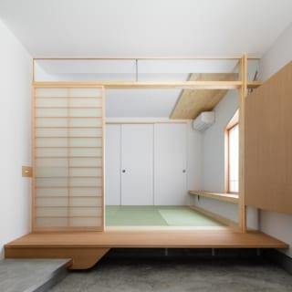 1階土間から和室を見る。障子の上の欄間にはガラスがはめてある。障子を閉めれば隙間なく空間を閉じることができ、エアコンの空気を逃すことなく快適に過ごせる。雨の日には傘を土間に広げ、乾いたら画像右のボックスへ収納。和室にも飾り棚をつけた