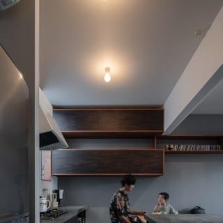 2階キッチン。螺旋シェルフと素材や色味を合わせた壁面収納は、ラインを強調するため扉をフラットにした