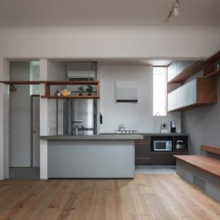 リビングダイニングからキッチンを眺める。調理関係の仕事をされていた奥様のために、床材をプロ仕様のモルタル仕上げにした。キッチンの天板はステンレスも考えたが、喫茶店というにはシャープすぎるとモルタルの研ぎ出し仕上げを採用し、全体的なトーンを合わせた