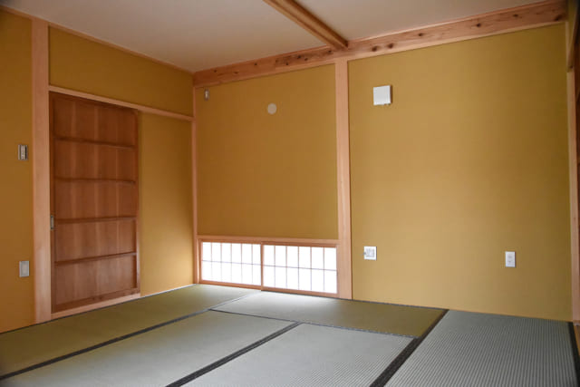 和室。板戸は浴室へと続いており、反対側にはトイレに続く板戸もある。木材は、縦に支える柱は桧、横に走る梁などは杉と使い分けた。手を触れる場所には、手あかなどが付きにくい桧がより適しているという。桧は色味が白っぽく、杉は赤味がかっていて表情の違いも楽しめる
