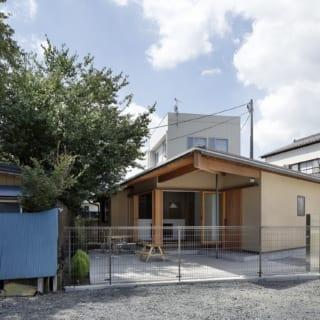 道路側の外観。蘆田さんは屋根の勾配をあえて緩やかに設計し、長閑な街並みに溶け込む控えめな印象のデザインにした。軒が大きく出た部分はコンクリート床の外土間。敷地と道路の間には隣地の駐車場があるため外土間は道路と離れており、プライベート感がある