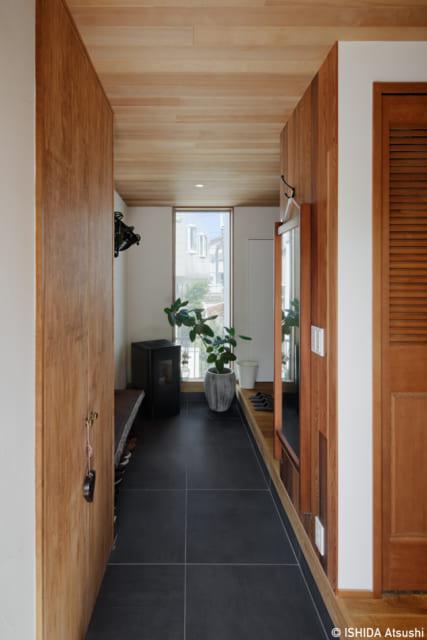 玄関を入ると長い土間。右の住空間側は壁がなくオープンだが、手前に収納があり邸内が丸見えにならない