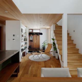 1階ダイニングからラウンジ、土間を見る。土間と住空間の間に壁はなく、1階全体が大きなワンルームのよう。写真中ほどにあるラウンジの造作収納の左側はパントリーで、キッチンと土間をつなぐ通路として使用可能。来客時は、正面のラウンジ側からゲストを迎える