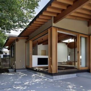 手前のコンクリート部分が外土間、写真右の引き戸が玄関、奥に見えるのがLDKの小下がり。屋根は外土間まで大きく伸びているため、小下がりと外土間は「1つ屋根の下」を地で行く一体感
