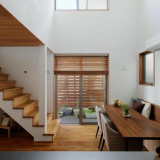 1階キッチンからダイニングを見る。ハイサイド窓のある吹抜けとオープンな階段のおかげで空間の高さを感じられ、住宅密集地とは思えないのびやかな開放感。ダイニングには造り付けのベンチがあるほか、階段もベンチ代わりになり、大勢のホームパーティーも気軽に楽しめる