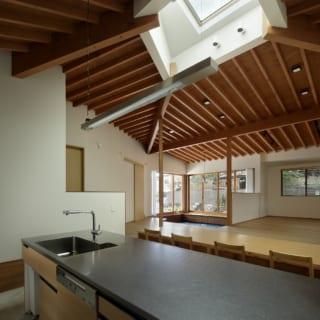 キッチンからダイニング、リビングを見る。キッチンカウンターはオリジナルで、天板ははマットな質感で高級感があるバイブレーション研磨のステンレス。左に見える腰高の壁の先はトイレなどの水まわり。低い壁によって、開放感を損ねることなく食卓と水まわりを区切っている