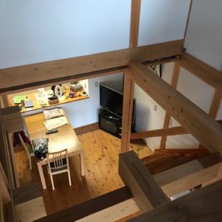 2階からキッチンを見下ろす。1階の天井と2階の梁が隣り合う部分は隙間を開け、軽快な印象を与えている