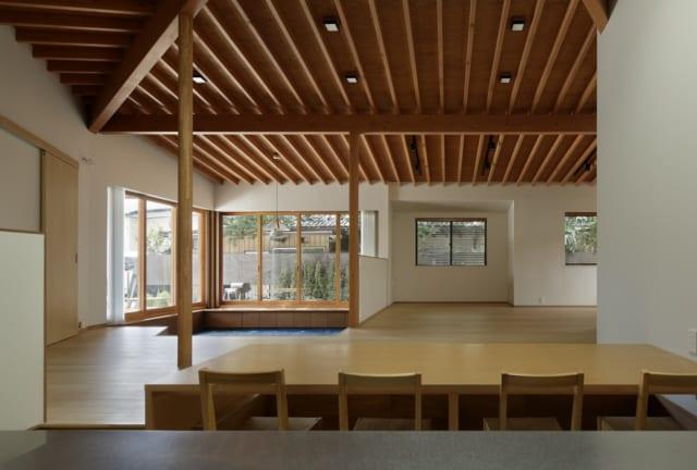 キッチン&ダイニングからLDKを見る。左奥の2面が大きく開口しているところが小下がり。ワンルームの大空間の中にホッと落ち着ける居場所があり、開放感や一体感を保ちながら思い思いにくつろげる。正面のフローリングスペースは、将来は壁を設けて子ども室にすることも可能