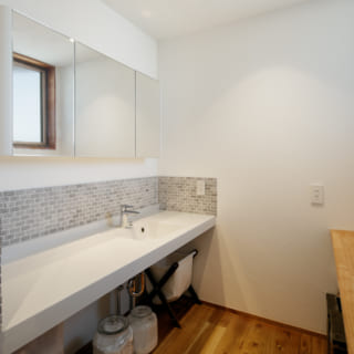 2階洗面室。床は板張り、壁の一部にはナチュラルな色合いのタイルをあしらって、洒落た雰囲気に