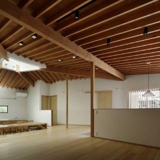 高い天井は屋根の構造がそのまま見える現し仕上げで、ワンルームの大空間に表情をつけている。垂木が整然と並びながらもアシンメトリーな4つの屋根面の絶妙なバランスが素晴らしく、建築としての奥深い美しさがある