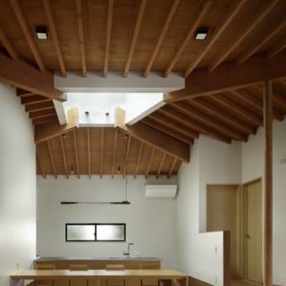 トップライトの下は造り付けのダイニングテーブル。奥のキッチンの床が低いため、手前は掘りごたつ式で座る