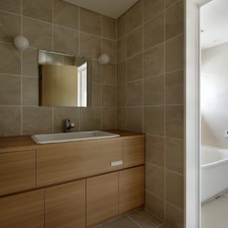 洗面室も木とタイルでナチュラルに。造作の洗面台には収納がたっぷり。洗面室の隣にある洗濯室も収納豊富