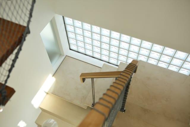 3階の階段から下を見る。「明るいけれども、人の視線などは気にならないようにしてほしい」との要望は、ガラスブロックをはめ込み解決した。外の景色が絵の具のパレットのように見え、室内から階段を見た景色の雰囲気も印象的なものになった