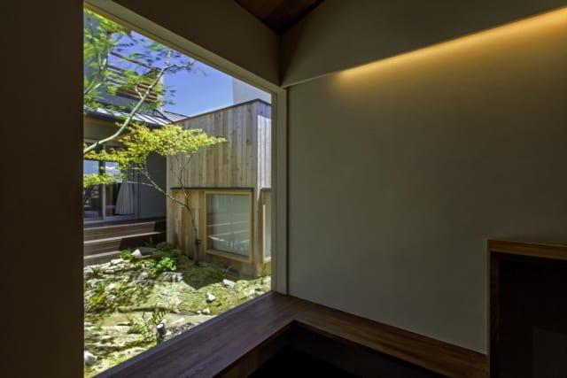 玄関から見た中庭の様子。備えられたベンチに腰掛け、庭を見ながらゆっくりと靴を履き替えることができる