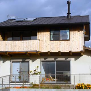 南から外観を見る。せがいは、左のバルコニー側が1200mm、右の窓側が910mm張り出しており、日射を十分に遮蔽する。I邸ではパッシブデザインを多く取り入れており、屋根の上に乗っているのは太陽熱給湯機のパネル