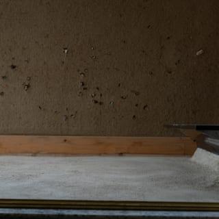 玄関の壁は、子どもたちが拾ってきた小石を投げつけて、おさえて作っている。三和土と踏み石は石材業を営むT様がご自身で施工。重く硬いスウェーデン産黒御影石の踏石は、薄く軽くみせるように意識し、タイトな玄関に静かに納まる印象に仕上げた。土壁は、四日市の左官職人、松木憲司さんの仕事によるもの