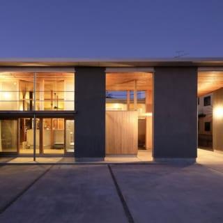 堤防側の外観。S邸は天然木材で仕上げた住空間を、外周部に並ぶモルタル仕上げの構造壁で囲った「入れ子の構成」。外周部の構造壁の間はガラスがはめられていないので、住空間の壁とのレイヤーが凹凸の陰影を生み出す。夜は照明によって陰影がいっそう際立ち、美しい佇まいに