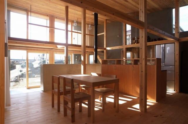 ダイニング。テーブル越しの腰高壁の奥がキッチン。天井高が最大4.6mもあるのびやかな住空間は南の堤防側が天井までの全面窓で、たっぷりと光が入る。空や堤防の緑を一望できるが、住空間は敷地の奥に配しているため堤防道路からの視線は通らず、プライバシーを確保している