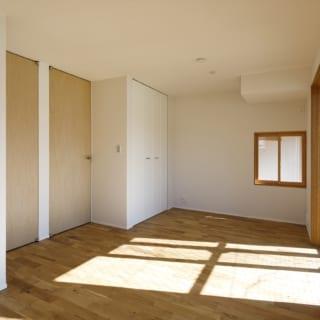 1階南側個室は光が豊かに入り明るい。将来的な使い勝手を考え、ドアも収納も2つずつ設置、真ん中で仕切れるようにしつらえた。奥の小窓からは階段下のスペースが見える
