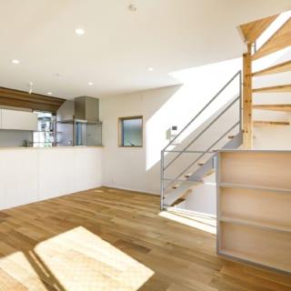 リビングからダイニングキッチンを見る。1階から2階に上がったところの階段の手すりは棚を造作し兼ね合わせた。棚の木口部分は手すりと同じ幅にしたほか、同じ色に塗装し、視覚的に手すりの一部分として捉えられる。デザインされた空間を堪能できるのも、渡辺さんのなせる業だ