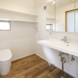 2階、洗面脱衣室。トイレの右横には、洗濯機を置く。鏡越しに見えるのは浴室のドア。水回りをコンパクトにまとめ、LDKのスペースに余裕ができた