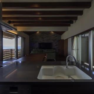 キッチン側から見たリビング。左手の窓の奥には真っ青な海の景色が広がっている
