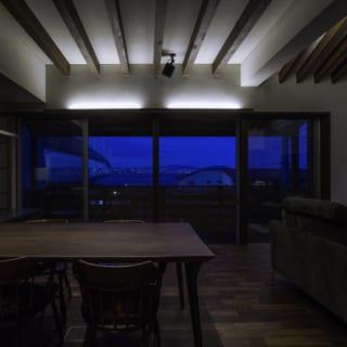 ダイニングの夜景。大きく開いた北側、開口部の外には、明石海峡大橋を望む。美しい景色を眺めながらダイニングテーブルを囲み、家族で食事を楽しむことができるつくりとなっている