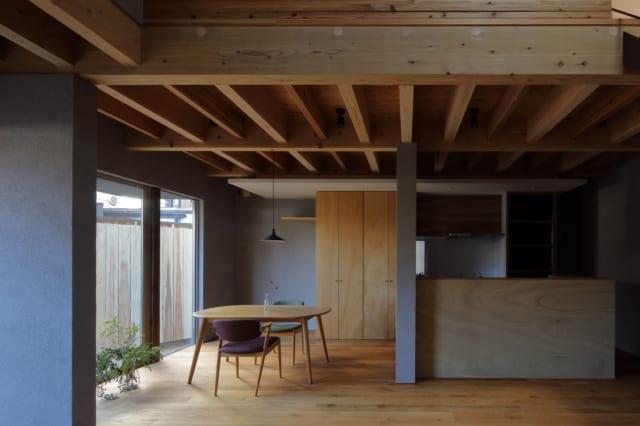 1階リビングからダイニング、キッチンを見る。壁は建物を支える力強さを表現し家に必要な安心感が生まれた。キッチンに立つと遮るものなく1階の空間が見渡せるほか、吹き抜けを通して2階の気配が届き家全体の様子を把握できる。正面中央、木製の造作収納はパントリーとして使用