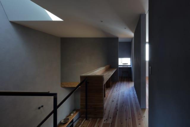 2階廊下。右の子ども部屋は将来、個室として仕切ることができる。「そのとき、勉強机を置くスペースが足りなくなるのでは」とつくったのが吹き抜けに沿ったスタディーテーブル。現在は家族で便利に使用している。扉は引き戸にし、画像のように開け放てば空間がフラットに繋がる