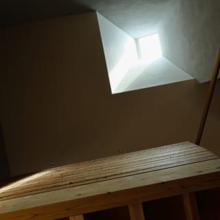 1階リビングから吹き抜け、トップライトを望む。小さく開口したトップライトから入った光は、メガホン状に広がる光の通り道を通って家全体を明るく照らす。光が全方向に広がるようにしたことで、2階の廊下にも光が届く