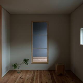 2階、主寝室からインナーバルコニーを見る。正面の扉には木製の片開き網戸を取り付け、行き来できるだけでなく扉を閉じたまま風を通すこともできる。インナーバルコニーは子ども部屋にも接して光を届けている。「思いがけず使いやすい場所。あってよかった」とH様もお喜びだ