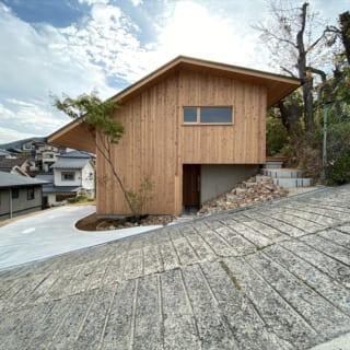 道路側から見たH邸の外観。土地を造成しない代わりに建物基礎を立ち上げ、建物自体で北側の土砂を受けられるよう工夫された
