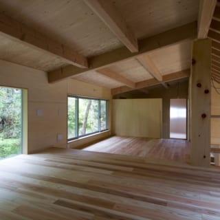 2階ベッドルームから見た景色。北側の森の景色を取り入れつつ、内装に杉を用い、「森の中の家」のような温もりある雰囲気を演出している