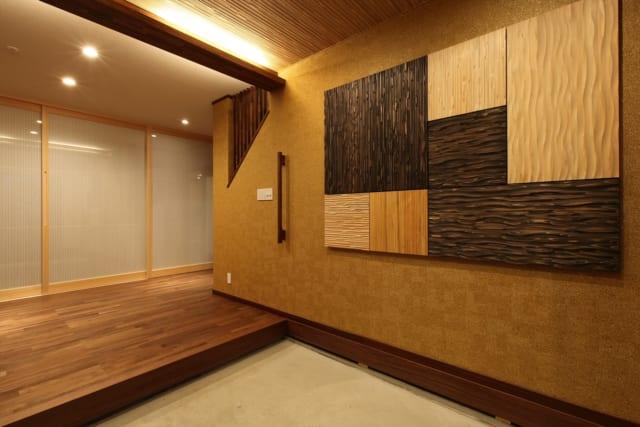 広々とした玄関。それぞれ色や模様の違った木を組み合わせて作ったオブジェが、お客様をお出迎え