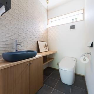 タイル敷きのトイレも広々とした空間に。片面の壁にはエコカラットを張ることで調湿・消臭に配慮した