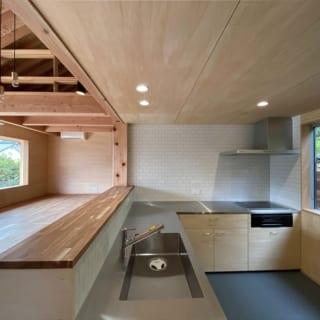 Hさんの希望で造作された、広いⅬ字型のキッチン。各部屋に収納がないため、キッチンの奥に広い収納スペースが用意された