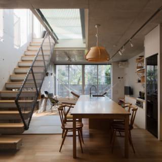 【C住戸】メゾネットを活かした吹抜けやテラスに面した大開口で、気持ちのよい明るさと開放感を創出。本来、壁から突き出した階段はコンクリートでつくるのが難しいが、奥野さんは入居者さまの好みに沿ってコンクリートで設計。表面には踏み板を張り、木の表情もプラス
