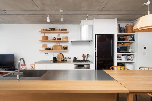 【C住戸】ダイニングで過ごすことが多いという入居者さまのライフスタイルに合わせて、LDKの中央にアイランドキッチンを配置。キッチンはセパレートで、奥の壁沿いにはコンロがある。写真右側は床を一段低くし、アイランドキッチンとテーブルの高さがそろうように調整