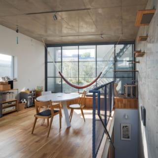 【E住戸】コンクリート×木の内装で少しインダストリアルな雰囲気に。テラス側はヨーロッパ風の格子窓