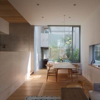 【A住戸】奥行きのある住空間の中ほどに中庭を設けた住戸(写真中央)。屋外の自然を間近に感じて暮らせる落ち着いた空間だ。リビング・ダイニングは床が地面より低いため、椅子に座ると緑が迫るように目に入る