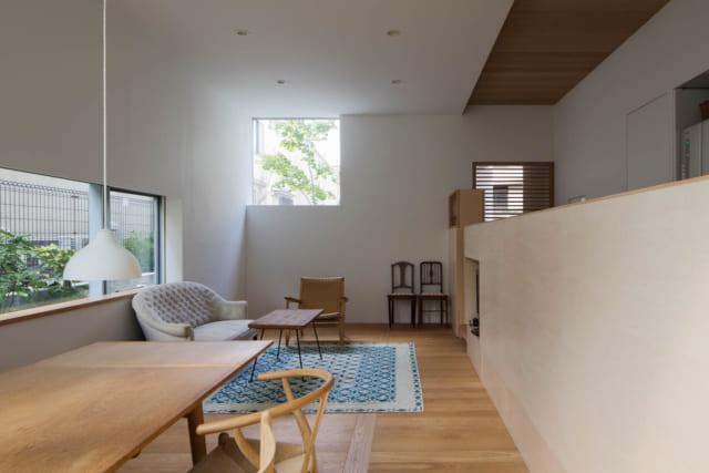 【A住戸】白い塗り壁と木目で仕上げた、ナチュラルな北欧風の空間。オーク材の床は途中で垂直に板を挟む朝鮮張り。垂直に張った板が境界線の役割を果たし、「ここまでがキッチン」「ここからリビング・ダイニング」と、適度にゾーニングされている