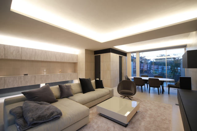リビングからキッチン、ダイニングを見る。間接照明のやさしい光で天井の美しい陰影が浮かび上がり、ホテルのラウンジのよう。写真左奥のタイル壁で囲われたスペースがキッチン。エアコンはキッチンの天井裏に設置し、LDK全体に空調が行き渡るようにしている