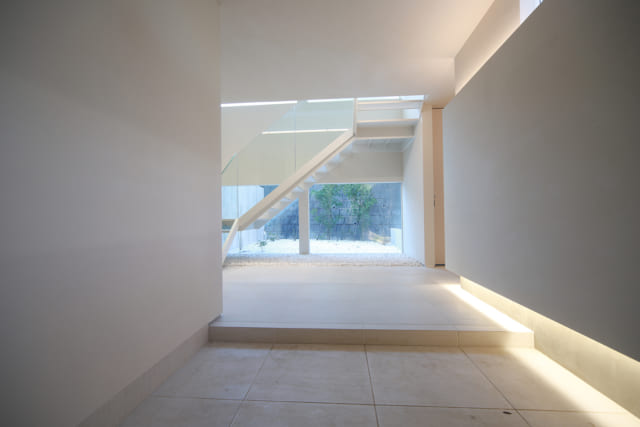 玄関ホールに入るといきなり「白の世界」に引き込まれ、美術館か高級アパレルショップに足を踏み入れたような錯覚を起こす。正面には浮遊感のあるオブジェのような階段。写真手前右の壁は少し厚みをもたせ、間接照明を入れている。おかげで玄関土間もすっきり洗練された印象に