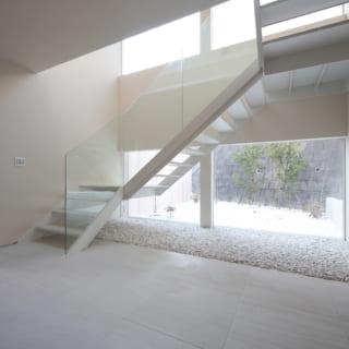 段差がゆるやかな階段で、玄関ホール全体がゆったりとした雰囲気に。階段沿いは隣家と視線がぶつかる部分だけ壁があり、上下は大きなガラス窓。吹抜け上部から明るい陽光が入ってくる。階段下は窓越しの庭と同じ白い砂利石が敷かれ、屋外とのつながりを感じられる