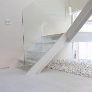 白い鉄骨階段は、ガラスの手すり、段差をつけて細く見せているササラ(階段側面の板)などで浮遊感を演出