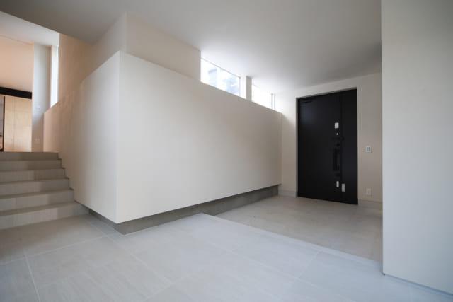 玄関ホールの階段側から玄関を見る。玄関ドアの左、壁の上の窓から漏れる光は中庭からの自然光。I邸は勾配のある敷地形状を活かしたスキップフロアで、写真左の階段をのぼった通路の先にLDKが広がる