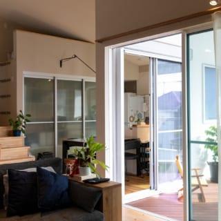 2階リビングからダイニング・キッチンの方向を見ると、テラスも住空間の一部のように感じられることがよくわかる。写真奥の引き戸はキッチン背後の収納。H邸はその場で使うものを入れる造作収納を各スペースに配した設計。モノが増えるのを自然に防げてすっきりと暮らせる